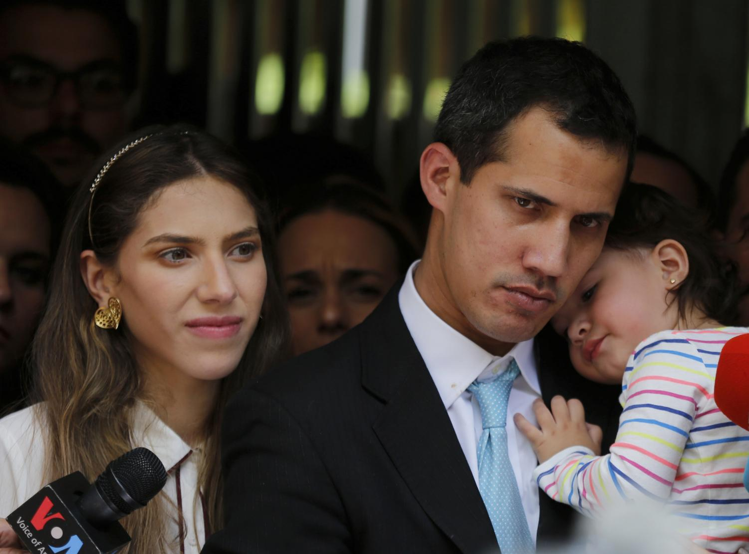 Opposition National Assembly President Juan Guaido, accompanied by his wife Fabiana Rosales and his 20-month-old daughter Miranda, listens to a reporter's question during a news conference outside their apartment, in Caracas, Venezuela, Thursday, Jan. 31, 2019.
