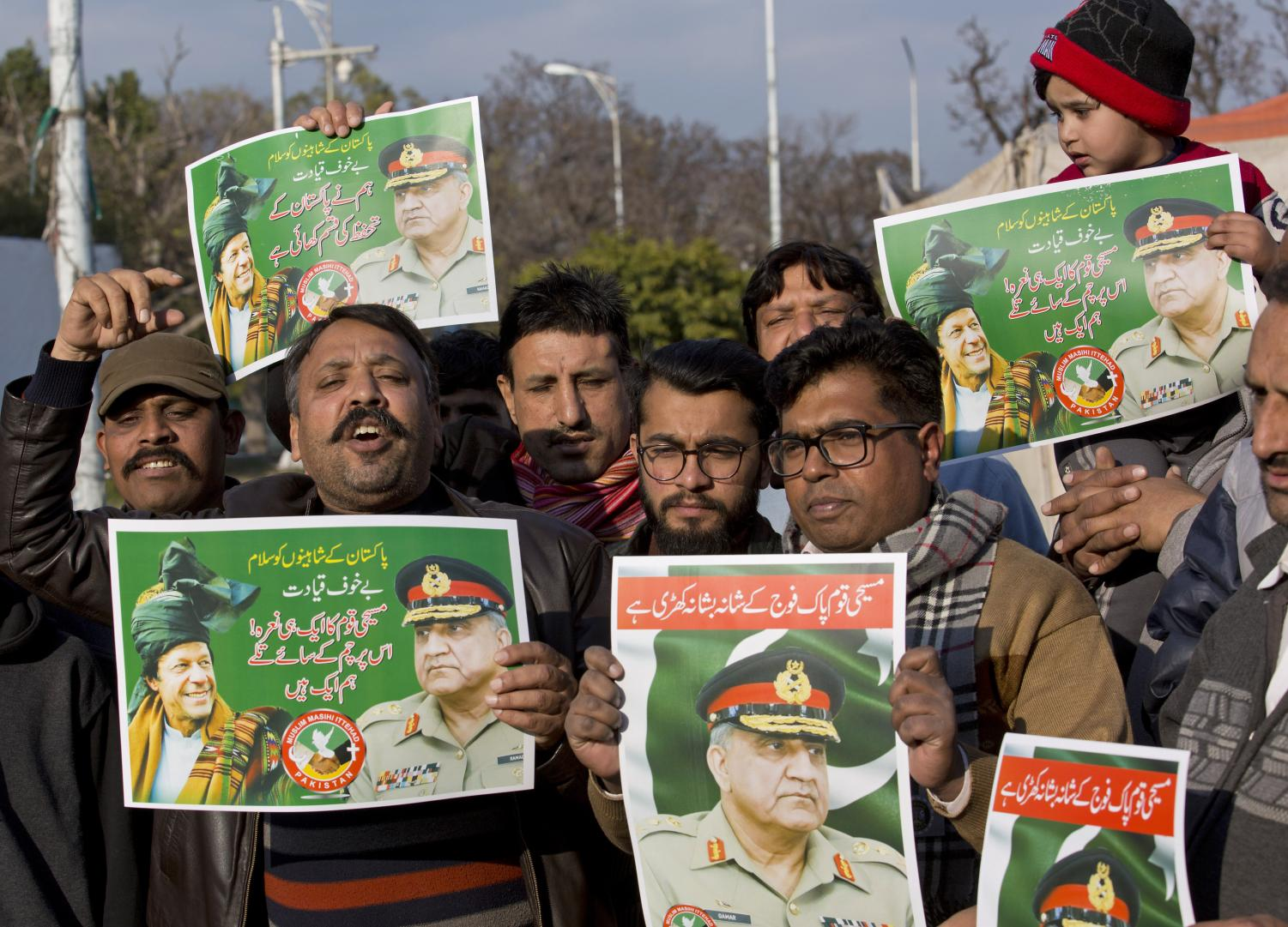 People hold posters of Pakistani army chief Gen. Qamar Javed Bajwa and Prime Minister Imran Khan during an anti-India rally, in Islamabad, Pakistan, Wednesday, Feb. 27, 2019.
