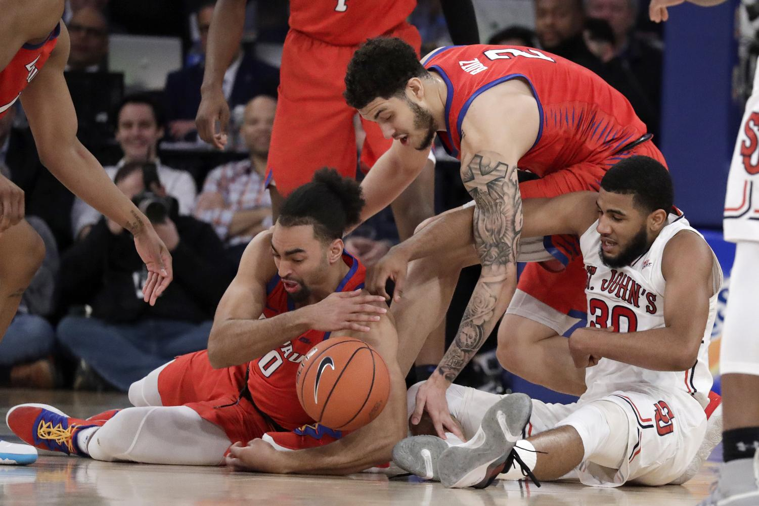 DePaul guard Lyrik Shreiner and sophomore forward Jaylen Butz scramble for a loose ball with St. John's guard LJ Figueroa during the second half of DePaul's Big East Tournament loss to the Red Storm. Julio Cortez | AP