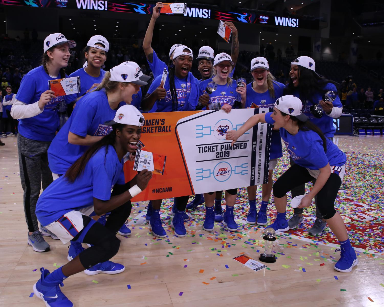 The+DePaul+players+pose+with+a+ticket+punched+poster+after+clinching+its+spot+in+the+NCAA+Tournament.+The+Blue+Demons+reached+the+tournament+for+the+17th+straight+season.+Alexa+Sandler+%7C+The+DePaulia