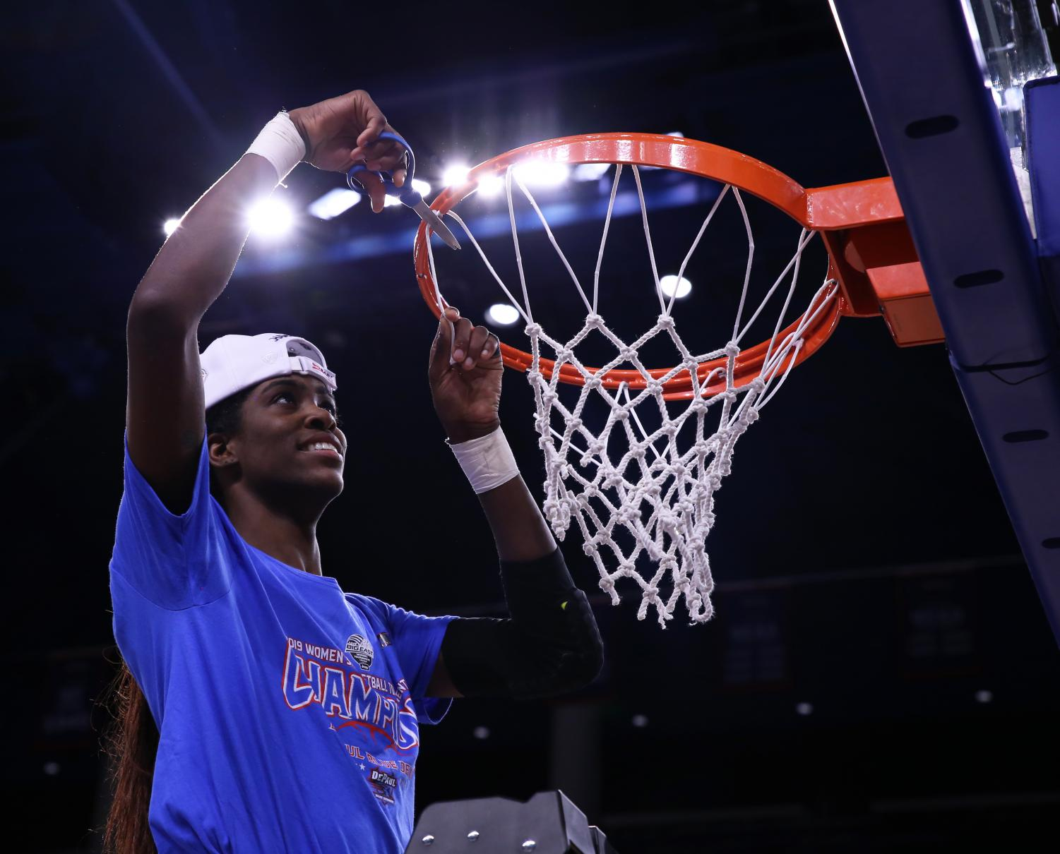 DePaul junior forward Chante Stonewall cuts down a piece of the net during DePaul's postgame celebration after defeating Marquette in Tuesday night's Big East Tournament championship game at Wintrust Arena. Alexa Sandler | The DePaulia