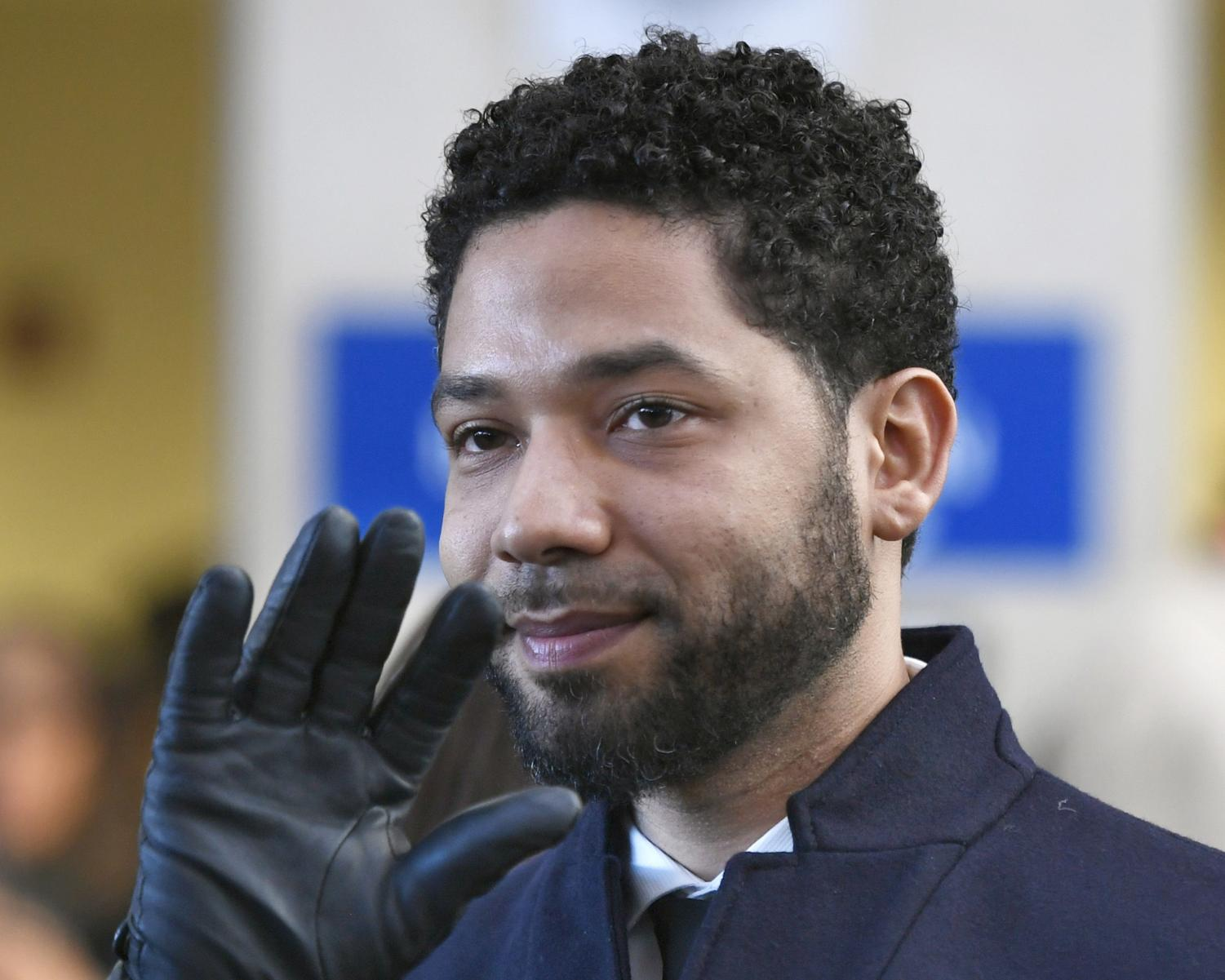 In this March 26, 2019, file photo, actor Jussie Smollett waves as he leaves Cook County Court after his charges were dropped in Chicago. A judge in Chicago has ordered the file in the Smollett criminal case unsealed. Cook County Judge Steven Watkins said Thursday, May 23, 2019, that while there are good arguments in favor of keeping the file sealed, the