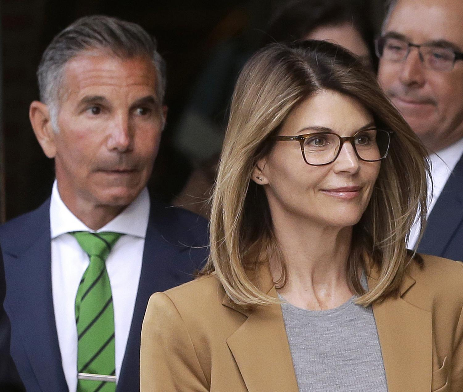Actress Lori Loughlin, front, and husband, clothing designer Mossimo Giannulli, left, depart federal court in Boston after facing charges in a nationwide college admissions bribery scandal. On Tuesday, April 9, Loughlin and Giannulli were among 16 prominent parents indicted on an additional charge of money laundering conspiracy in the case. (AP Photo/Steven Senne, File)