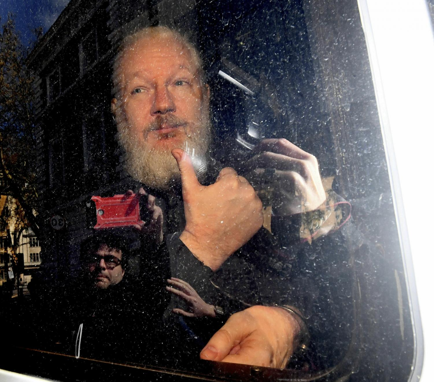 Julian Assange gestures as he arrives at Westminster Magistrates' Court in London, after the WikiLeaks founder was arrested by officers from the Metropolitan Police and taken into custody Thursday April 11, 2019. Police in London arrested WikiLeaks founder Assange at the Ecuadorean embassy Thursday, April 11, 2019 for failing to surrender to the court in 2012, shortly after the South American nation revoked his asylum.