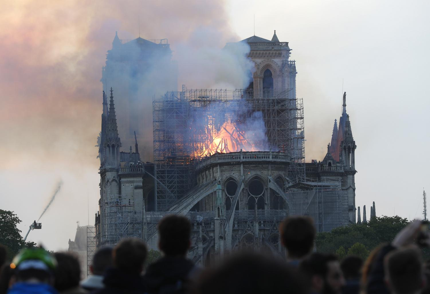 Flames rise from Notre Dame cathedral as it burns in Paris, Monday, April 15, 2019. Massive plumes of yellow brown smoke is filling the air above Notre Dame Cathedral and ash is falling on tourists and others around the island that marks the center of Paris.
