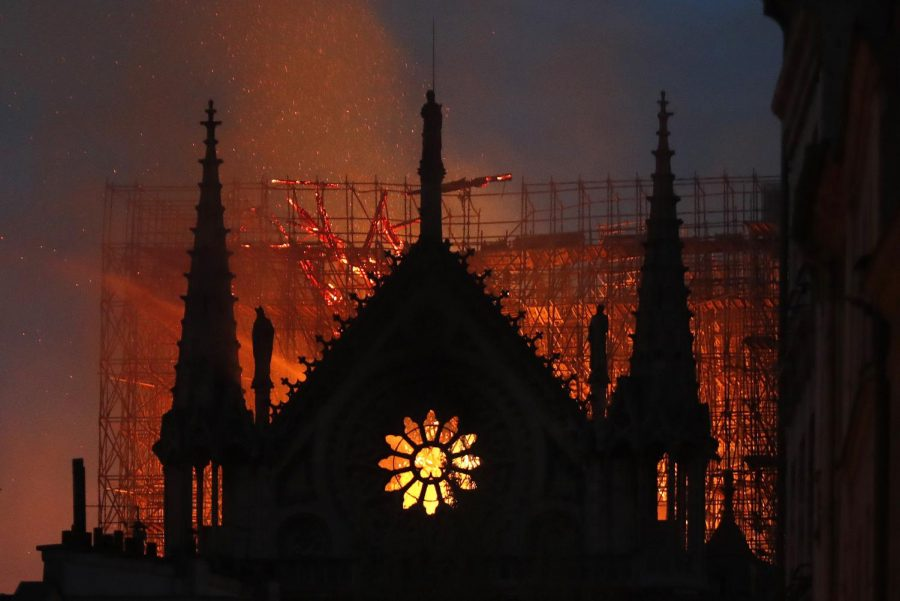 Fire+burns+inside+Notre+Dame+cathedral+the+night+of+April+15%2C+surrounded+by+the+scaffolding+for+a+previously+ongoing+renovation.+Ash+from+the+cathedral+fell+on+tourists+and+passersby+throughout+the+day.
