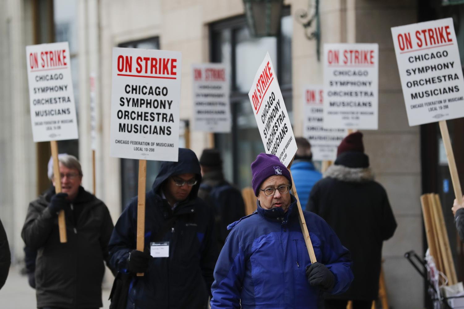 In this Monday, March 11, 2019 file photo, striking Chicago Symphony Orchestra musicians walk the picket line outside of Symphony Center in Chicago. On Saturday, April 27, 2019, negotiators for the Chicago Symphony Orchestra and musicians said they have reached an agreement to end the seven-week strike.