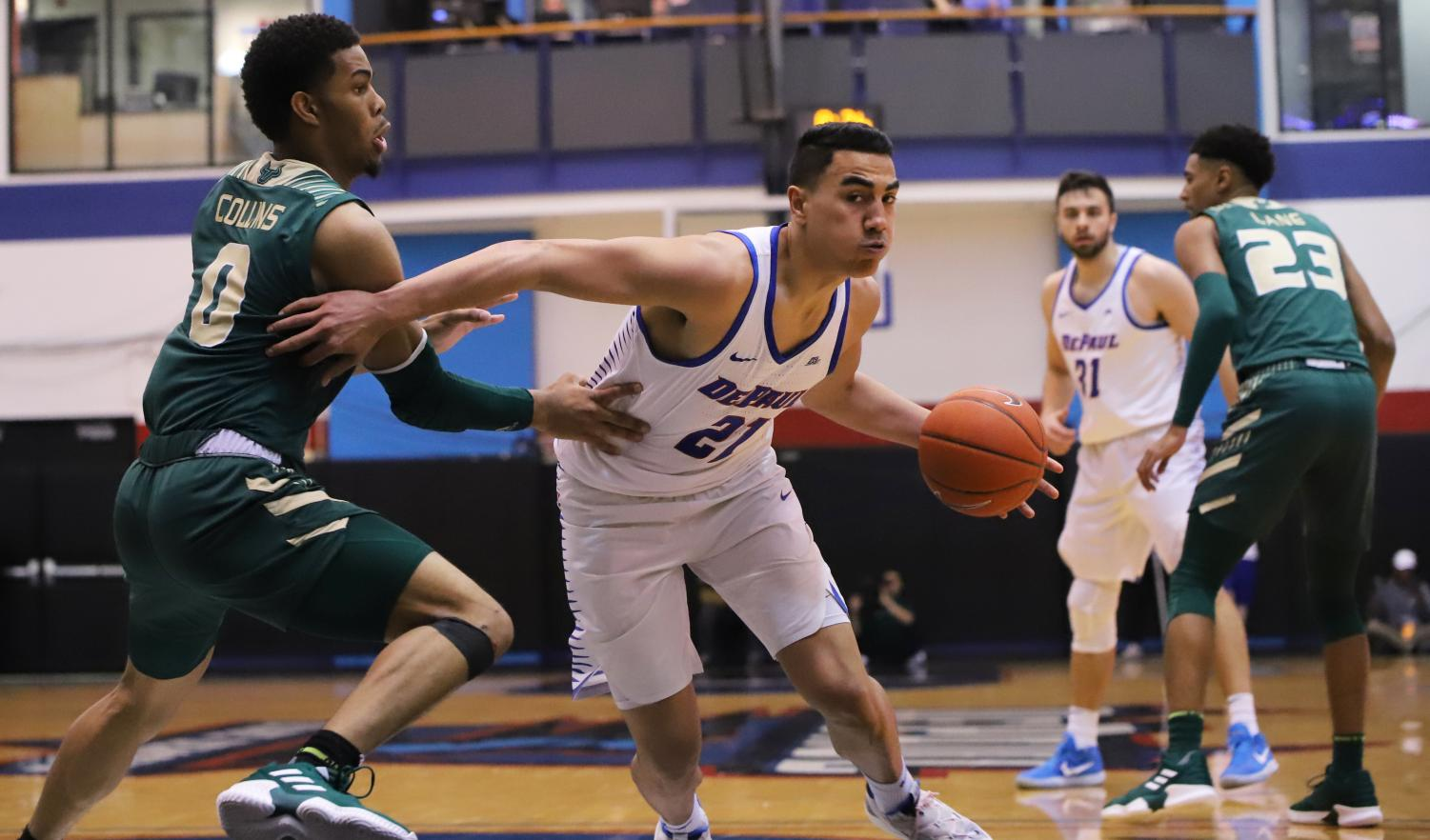 DePaul freshman guard Flynn Cameron drives past USF's David Collins during game two of the CBI championship series. (Alexa Sandler | The DePaulia)