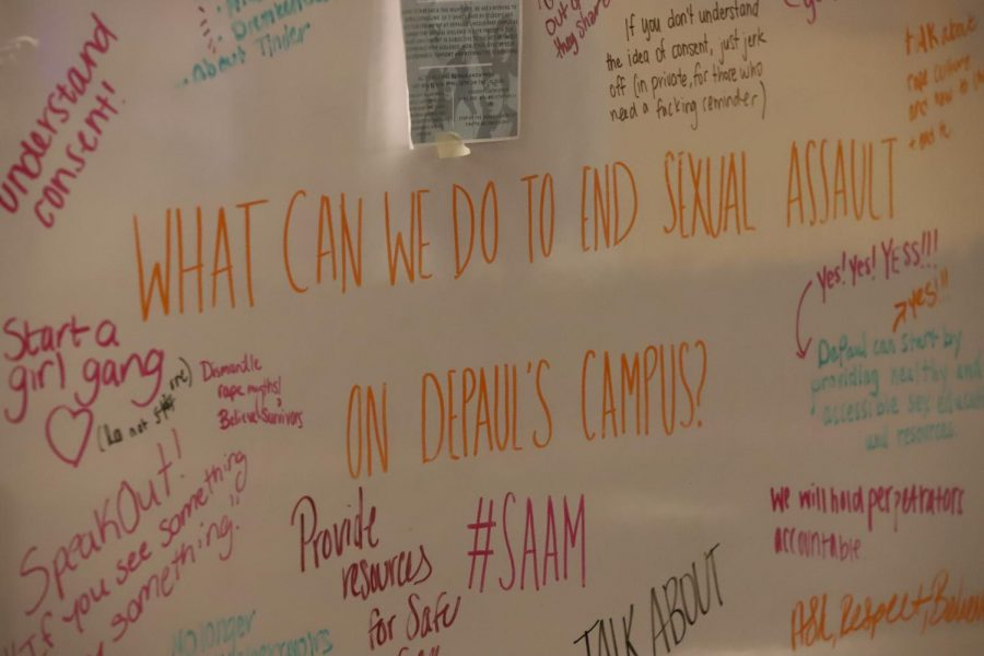 Students write suggestions for how to curb sexual assault on campus on a white board at the Take Back the Night event.