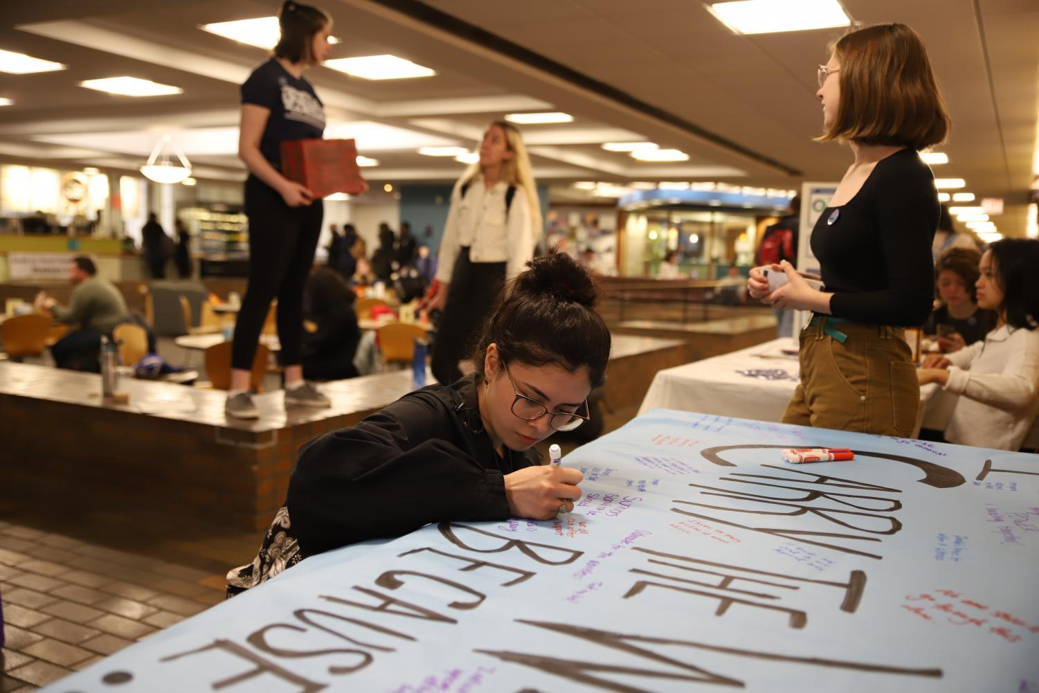 Vanessa Garcia, a freshman secondary education and English major, signs a poster expressing her support for victims of sexual abuse.