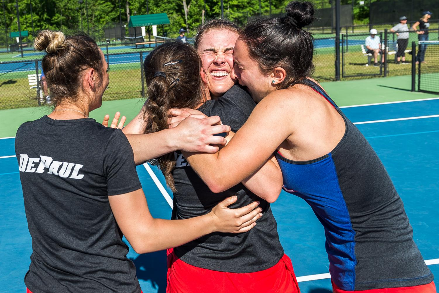 Three DePaul women's tennis players celebrate together after winning the Big East Tournament on April 22 in South Carolina. DePaul defeated Xavier 4-3 in the finals.