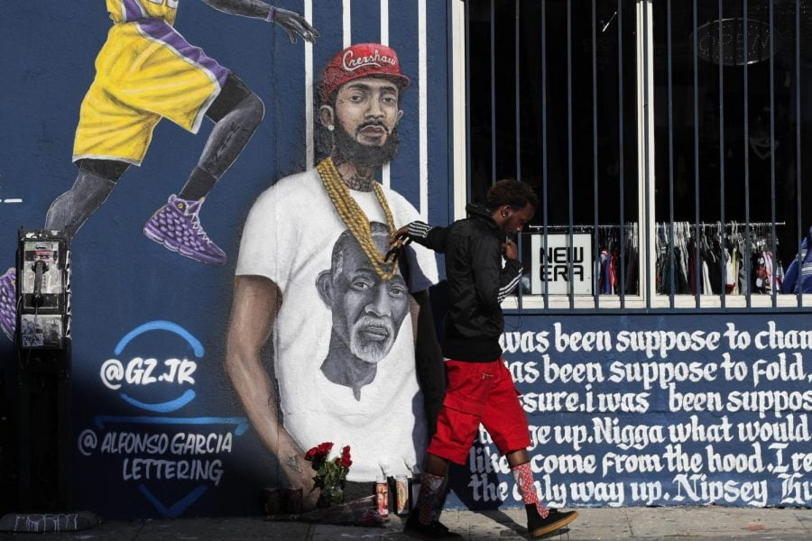 A+man+touches+a+mural+in+Los+Angeles+depicting+Hussle+on+April+2%2C+two+days+after+his+death.+Courtesy+of+Associated+Press.