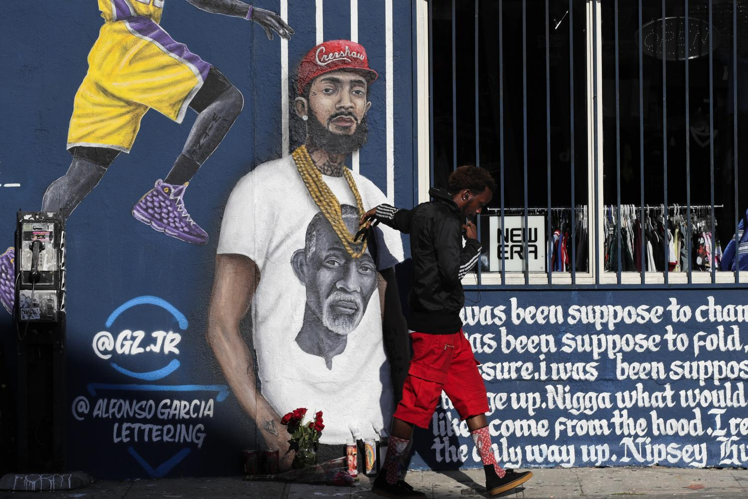A man touches a mural in Los Angeles depicting Hussle on April 2, two days after his death. Courtesy of Associated Press.