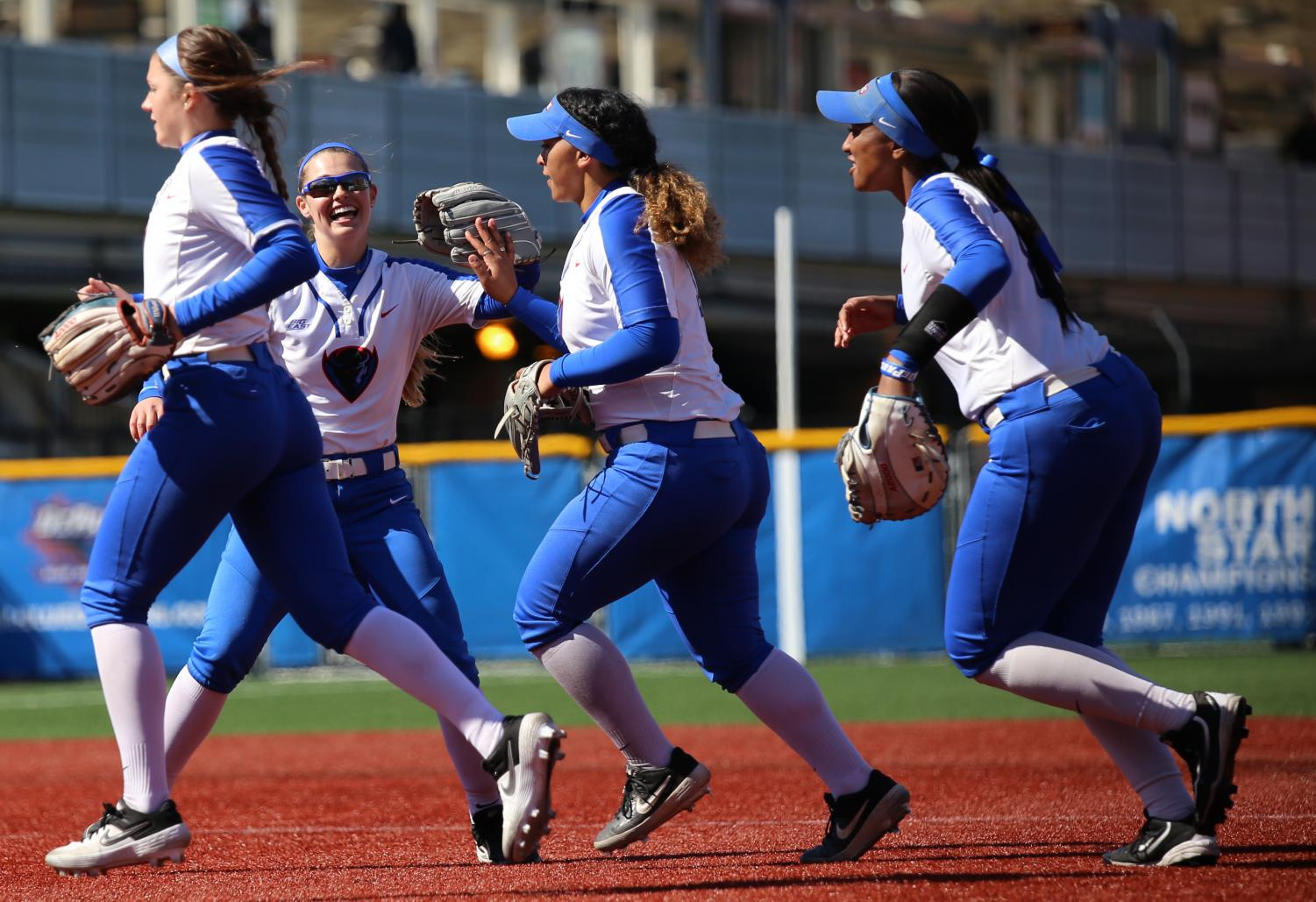 (Left to right) Skylor Hilger, Angela Scalzitti, Erin Andris and Morgan Greenwood celebrate the end of an inning against Providence at Cacciatore Stadium on April 13.