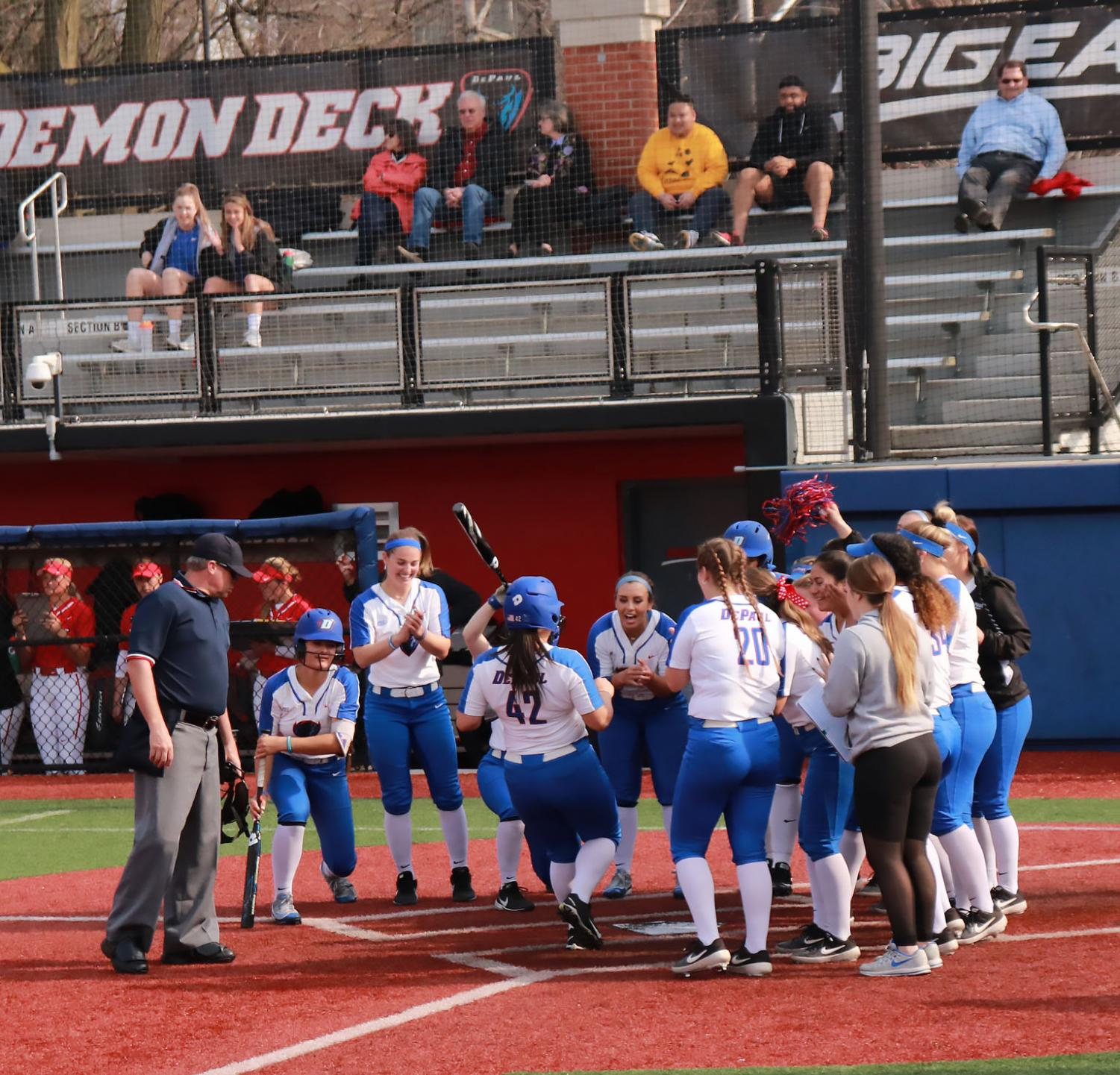 The DePaul softball team celebrates at home plate after the game winning run was driven in extra innings. DePaul defeated Illinois State 6-5 on Tuesday at Cacciatore Staduim Maria Guerrero/ The DePaulia