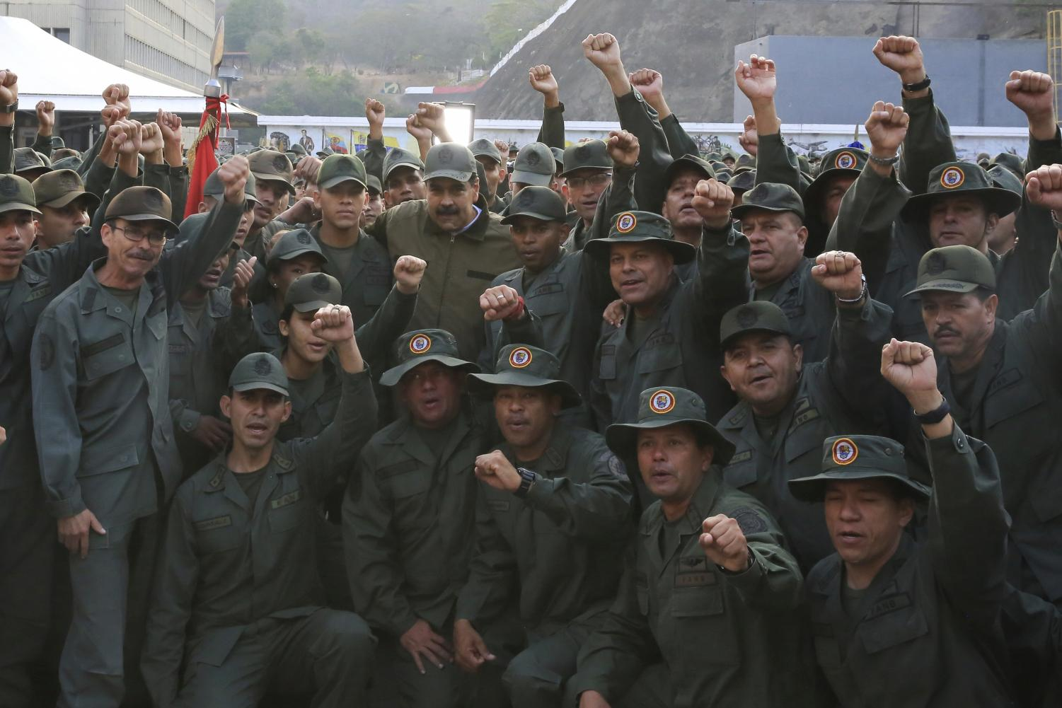 In this photo released by Miraflores Press Office, Venezuela's President Nicolas Maduro, center left, poses for a photo with troops at Fort Tiuna, in Caracas, Venezuela, Thursday, May 2, 2019. Flanked by commanders, Maduro said Thursday that the military must be prepared to combat