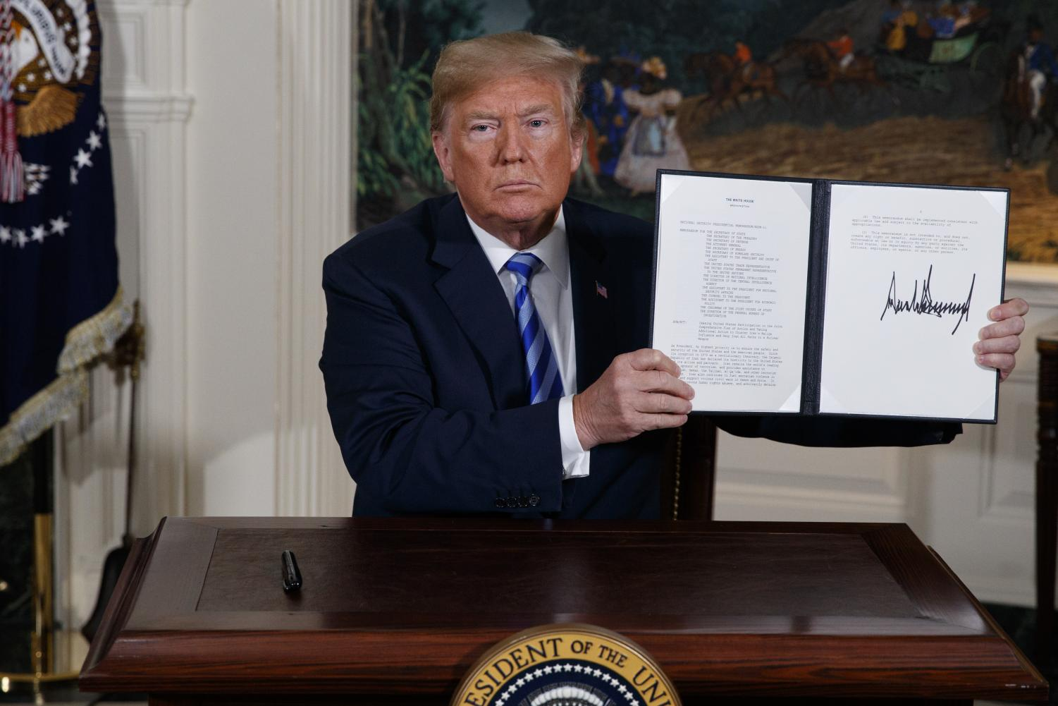 In this May 8, 2018 file photo President Donald Trump shows a signed Presidential Memorandum after delivering a statement on the Iran nuclear deal from the Diplomatic Reception Room of the White House. Iranian President Hassan Rouhani is reportedly set to announce Wednesday, May 8, 2019, ways the Islamic Republic will react to continued U.S. pressure after President Donald Trump pulled America from Tehran's nuclear deal with world powers.