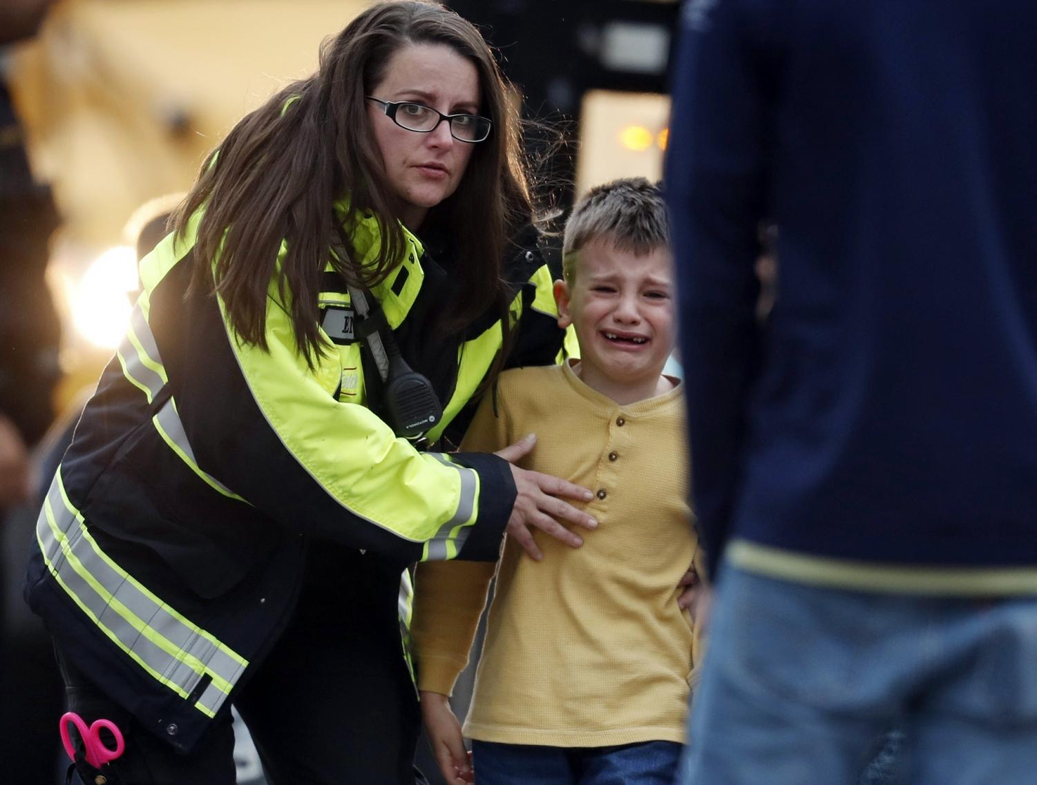 Officials guide students off a bus and into a recreation center where they were reunited with their parents after a shooting at a suburban Denver middle school Tuesday, May 7, 2019, in Highlands Ranch, Colo.
