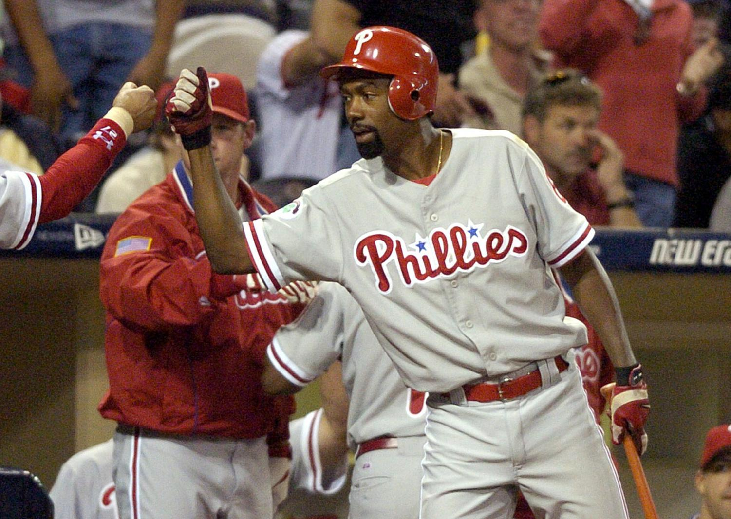 In this Aug. 5, 2004, file photo, Philadelphia Phillies' Doug Glanville congratulates a teammate in the 10th inning against the San Diego Padres in San Diego. The Chicago Cubs say they're investigating a fan using what appeared to be an offensive hand gesture associated with racism behind Glanville, now a television reporter, who was on the air for NBC Sports Chicago.