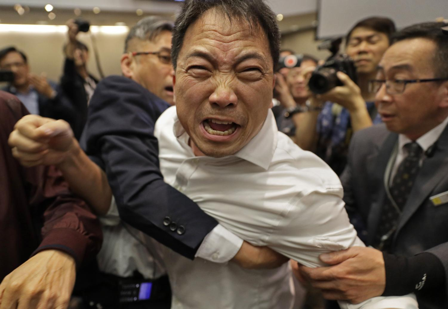 Pro-democracy lawmaker Wu Chi-wai is held by security guards at Legislative Council May 11.
