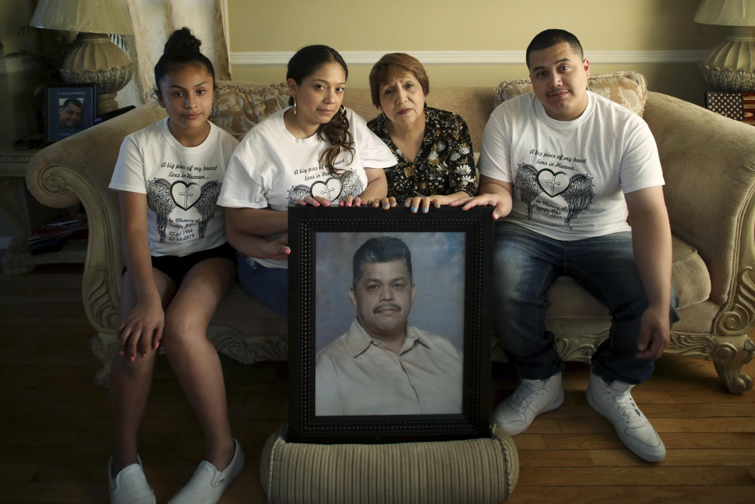 In this Wednesday, May 22, 2019 photo, family members of Vicente Juarez, including from left to right, his granddaughter Dyani (cq), 12, daughter Diana, wife Leticia and son Christian, pose for a photograph with a portrait of Juarez at their home in Oswego, Ill. Juarez was one of five people fatally shot by a coworker on Feb. 15 at the Henry Pratt Co. in Aurora. A Chicago Tribune investigation suggests that tens of thousands of Illinois residents whose gun licenses have been revoked could still have firearms. The problem was underscored in February's Aurora shooting when the shooter used a gun he kept despite the revocation of his Firearm Owner's Identification card in 2014.