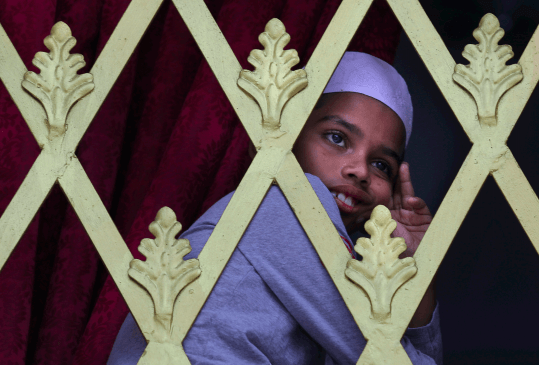 In this Friday, April 26, 2019 file photo, a Sri Lankan Muslim boy looks out from the window of a Mosque before Friday prayers in Colombo, Sri Lanka. Authorities had told Muslims to pray at home rather than attend communal Friday prayers that are the most important religious service for the faithful.