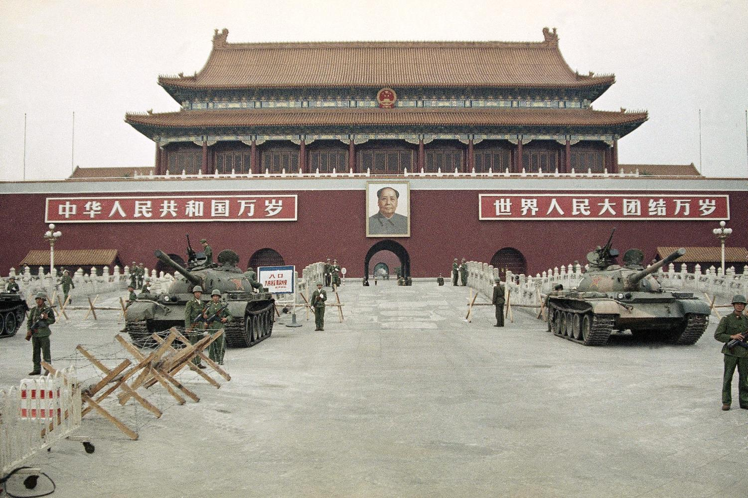 In this June 10, 1989 file photo, People's Liberation Army (PLA) troops stand guard with tanks in front of Tiananmen Square after crushing the students pro-democracy demonstrations in Beijing. Thirty years since the Tiananmen Square protests, China's economy has catapulted up the world rankings, yet political repression is harsher than ever.