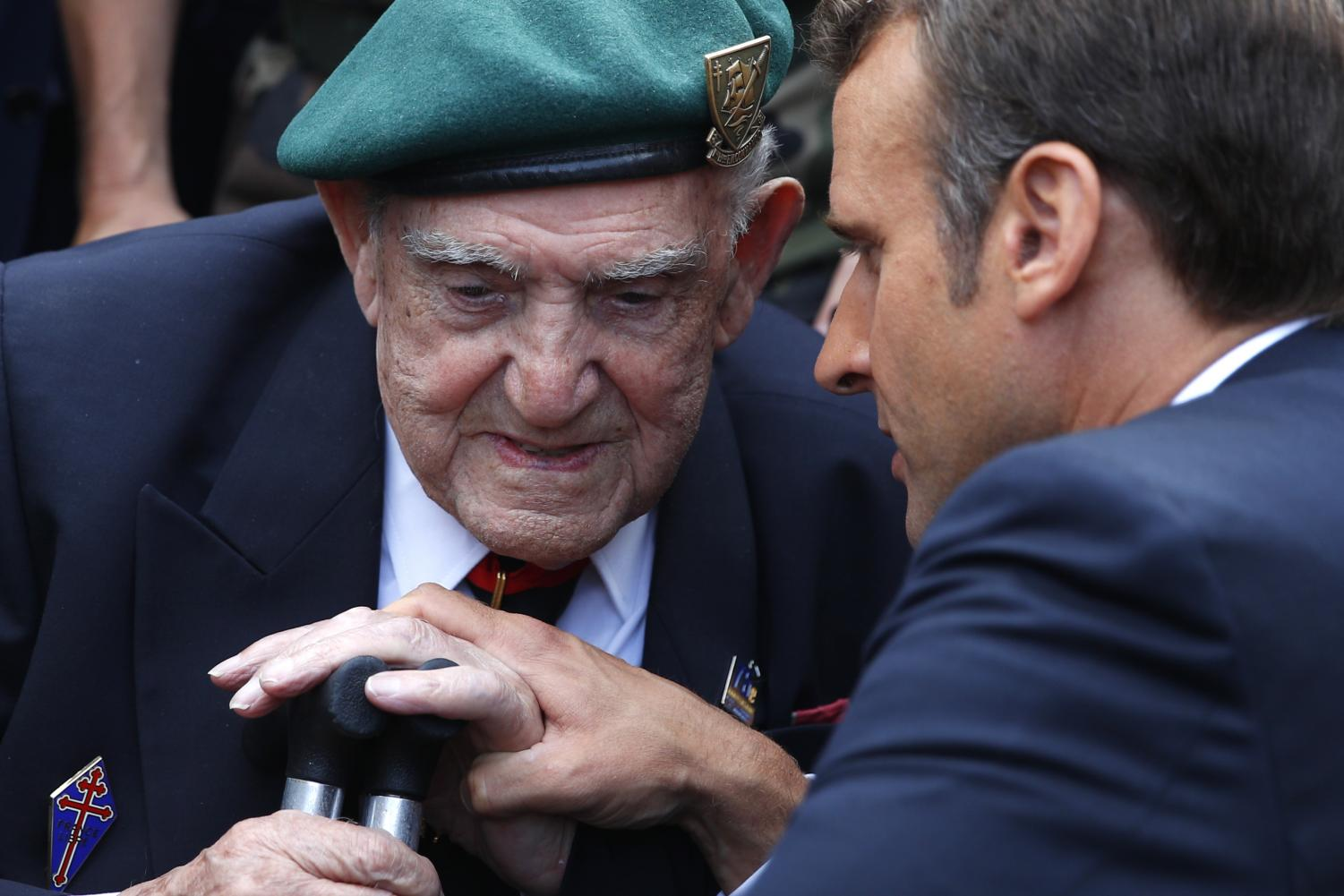 French President Emmanuel Macron, right, talks to French war veteran Leon Gautier, a member of the Kieffer commando, during a ceremony to pay homage to the Kieffer commando, Thursday, June 6, 2019 in Colleville-Montgomery, Normandy. The Kieffer commando, an elite French unit, was among the first waves of Allied troops to storm the heavily defended beaches of Nazi-occupied northern France, beginning the liberation of western Europe.