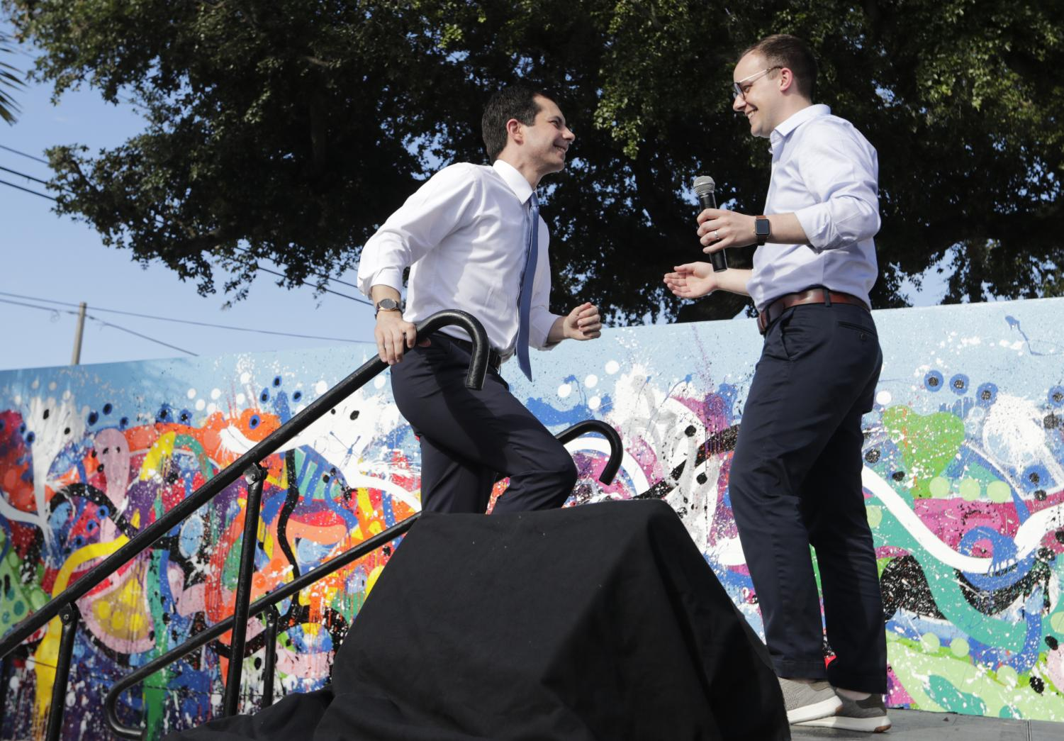 In this May 20, 2019, file photo, Democratic presidential candidate Pete Buttigieg, the mayor of South Bend, Ind., left, is introduced by his husband Chasten Buttigieg, right, during a fundraiser at the Wynwood Walls, in Miami. Buttigieg knows firsthand the burden of six-figure student loan debt. He and his husband have loans of more than $130,000, placing them in the ranks of the 43 million Americans who owe federal student debt.