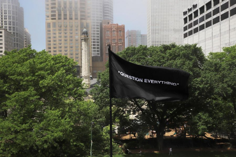 "Next to the street in front of the Museum of Contemporary Art waves a black flag inscribed with the words, ""Question Everything."""
