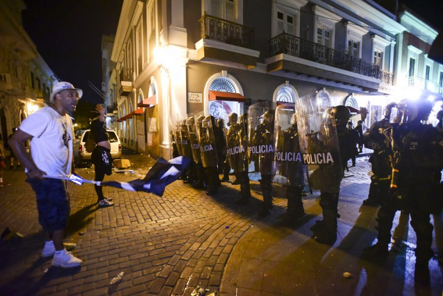 Demonstrators stand in front of riot control units during clashes in San Juan, Puerto Rico, Monday, July 22, 2019. Protesters are demanding Gov. Ricardo Rossello step down following the leak of an offensive, obscenity-laden online chat between him and his advisers that triggered the crisis.