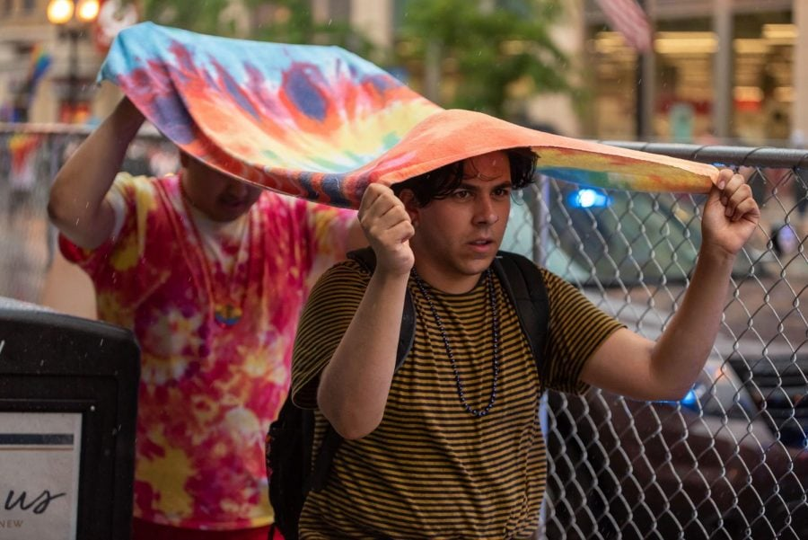 Parade attendees use a blanket to avoid the rain that caused the annual Chicago Gay Pride Parade to be canceled on Sunday.