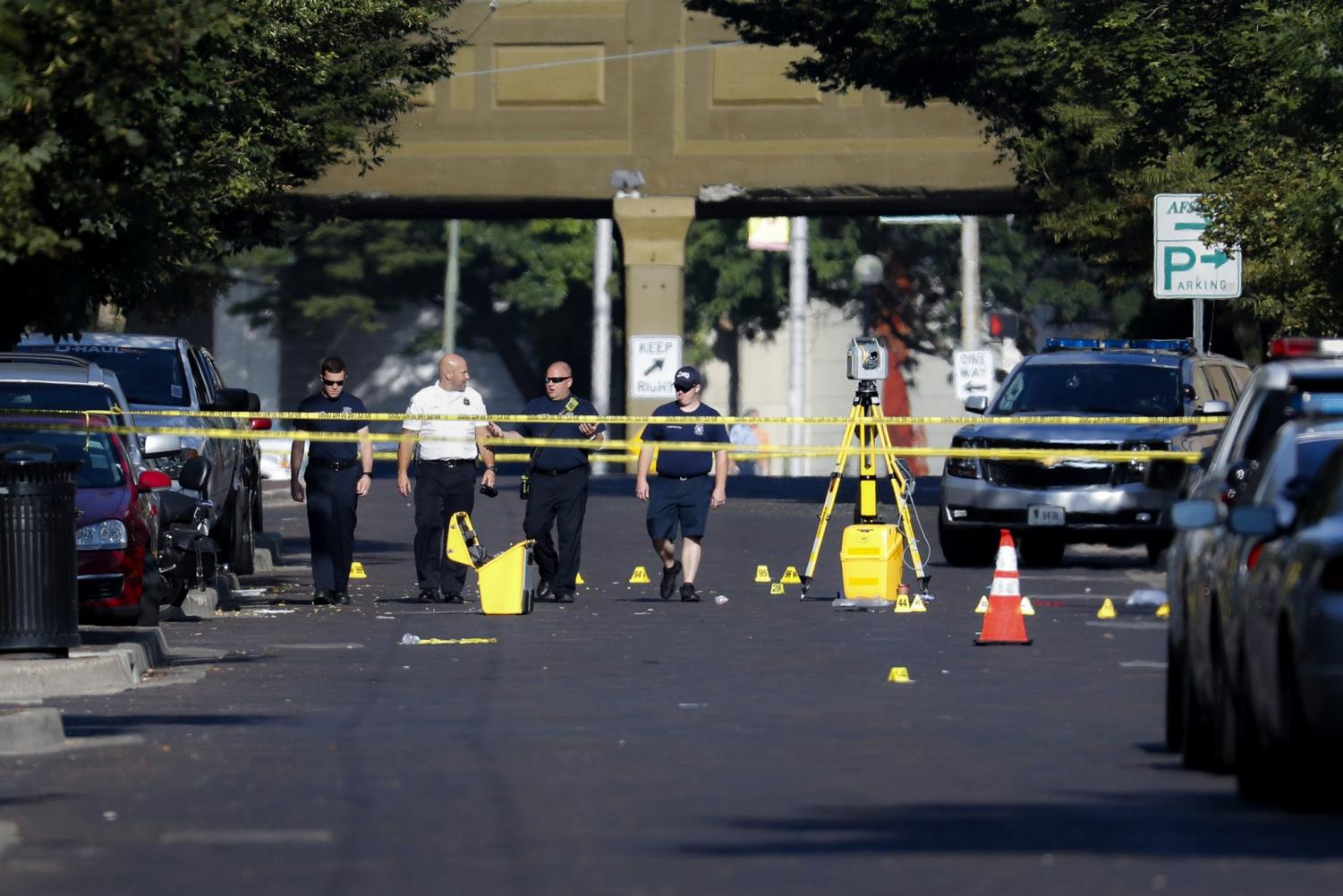Authorities walk among evidence markers at the scene of a mass shooting, Sunday, Aug. 4, 2019, in Dayton, Ohio. Severral people in Ohio have been killed in the second mass shooting in the U.S. in less than 24 hours, and the suspected shooter is also deceased, police said.