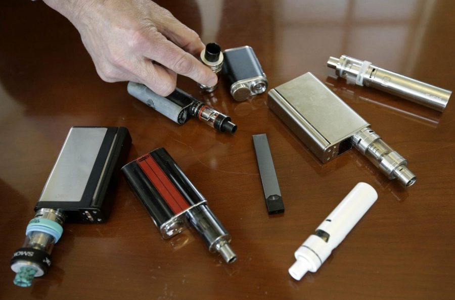 Marshfield High School Principal Robert Keuther displays vaping devices that were confiscated from students in such places as restrooms or hallways at the school in Marshfield, Mass. Illinois health officials are reporting what could be United States' first death tied to vaping. In a Friday, Aug. 23, 2019, news release, the Illinois Department of Public Health says a person who recently vaped died after being hospitalized with