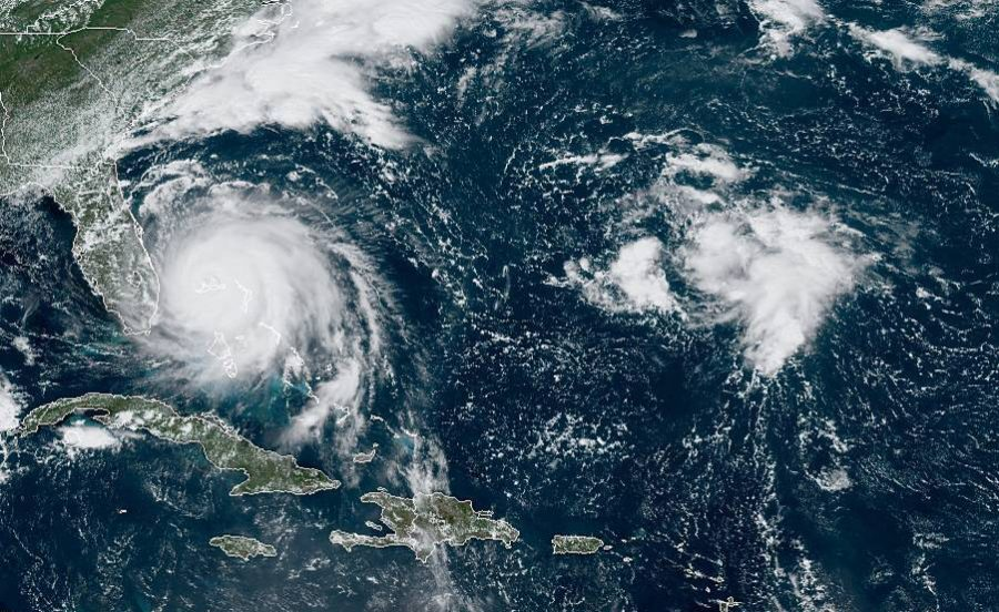 This GOES-16 satellite image taken Monday, Sept. 2, 2019, at 16:40 UTC and provided by National Oceanic and Atmospheric Administration (NOAA), shows Hurricane Dorian, left, churning over Bahamas. Hurricane Dorian hovered over the Bahamas on Monday, pummeling the islands with a fearsome Category 4 assault that forced even rescue crews to take shelter until the onslaught passes. (NOAA via AP)