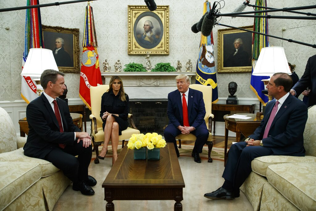 President Donald Trump talks about a plan to ban most flavored e-cigarettes, in the Oval Office of the White House, Wednesday, Sept. 11, 2019, in Washington. From left, acting FDA Commissioner Ned Sharpless, first lady Melania Trump, Trump, and Secretary of Health and Human Services Alex Azar.
