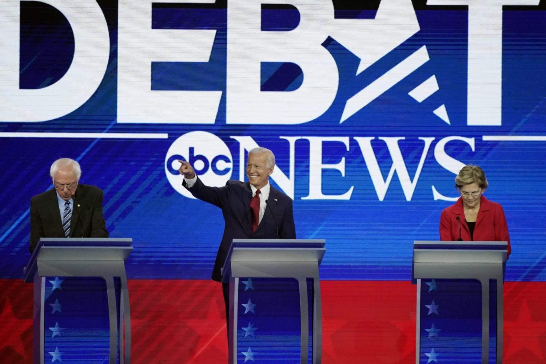Former Vice President Joe Biden, center, smiles at the audience during the Democratic primary debate on September 12. Senators Bernie Sanders and Elizabeth Warren are seen taking notes.