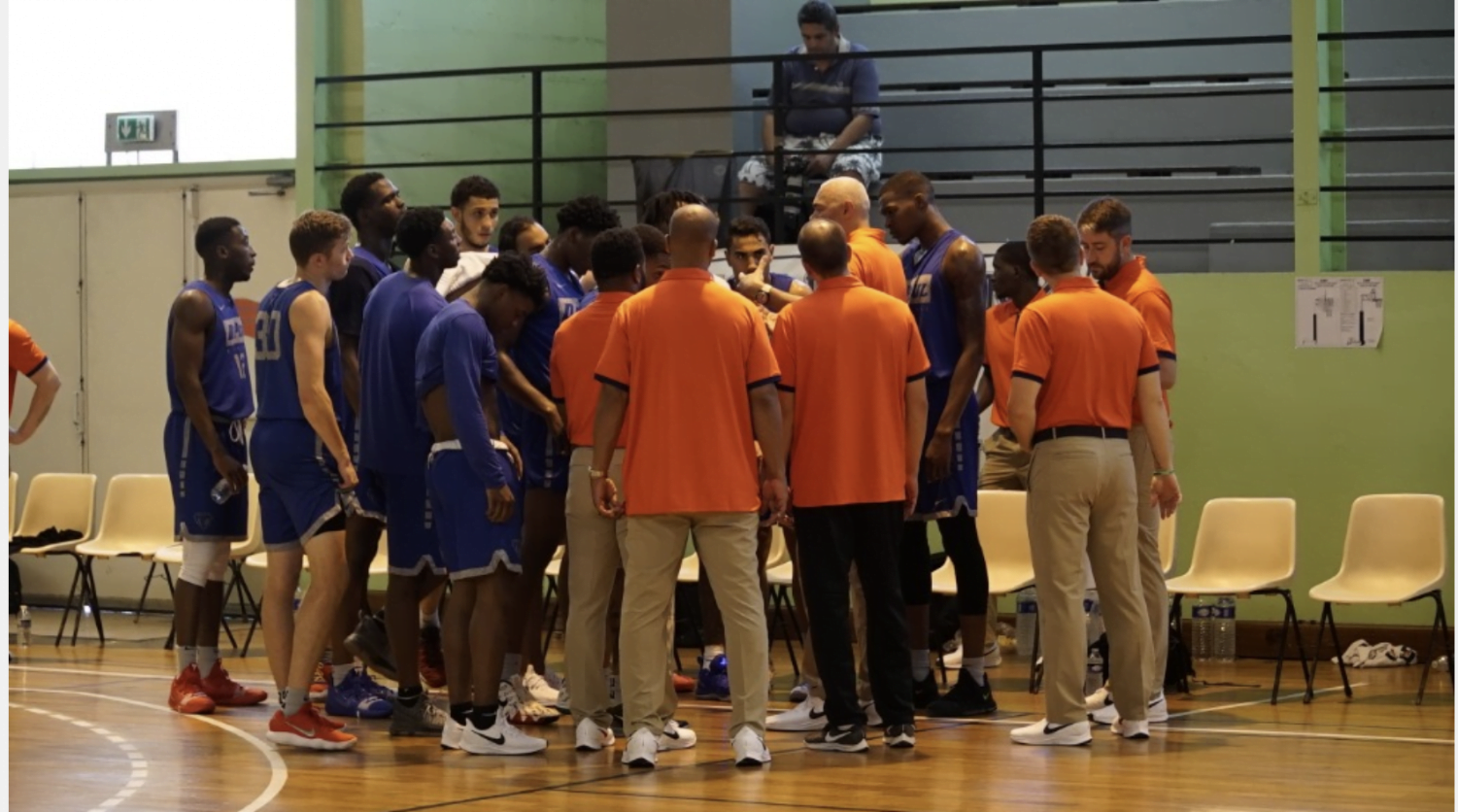 The DePaul men's basketball team huddles up around head coach Dave Leitao during a timeout in the first half. The Blue Demons defeated the Paris PK All Stars 118-56 on Aug. 8.
