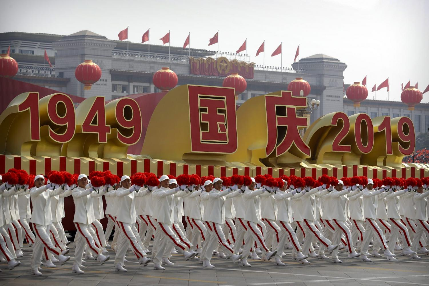 Participants wave flowers as they march next to a float commemorating the 70th anniversary of the founding of Communist China during a parade in Beijing, Tuesday, Oct. 1, 2019.