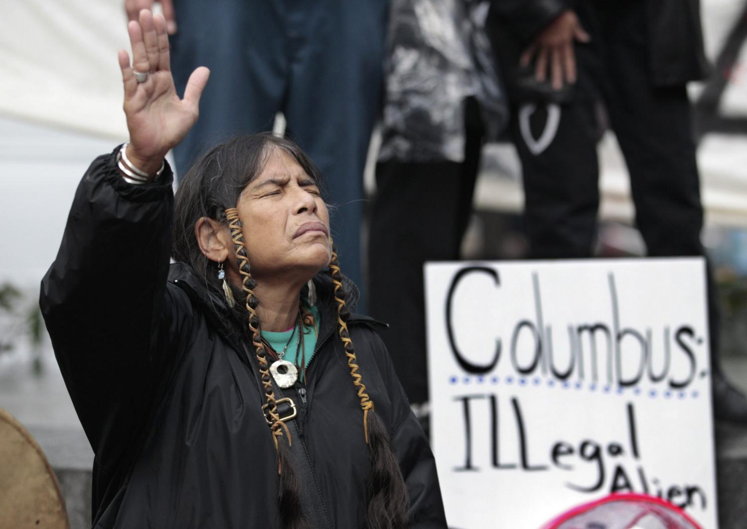 In this Monday, Oct. 10, 2011 file photo, Ferntree, of Duncan, British Columbia, a member of the Cowichan Tribes, holds her hand up as a prayer is given during a Native American protest against Columbus Day in Seattle.