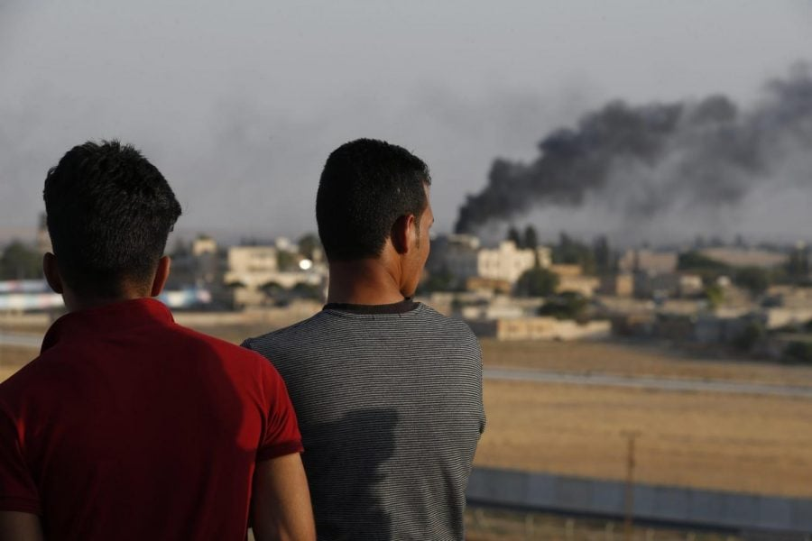 People standing on a rooftop in Akcakale, Sanliurfa province, southeastern Turkey, at the border with Syria, watch as in the background smoke billows from fires caused by Turkish bombardment in Tal Abyad, Syria, Sunday, Oct. 13, 2019.