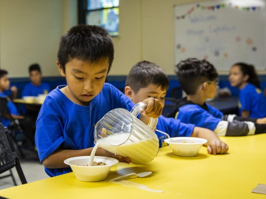 A+student+pours+milk+on+his+cereal+as+Mayor+Lori+Lightfoot+passes+out+breakfast+to+Chicago+Public+Schools+students+at+a+contingency+site%2C+Gads+Hill+Center+Friday%2C+Oct.+18%2C+2019.+Striking+Chicago+teachers+have+returned+to+the+picket+lines+for+a+second+day+as+union+and+city+bargainers+try+to+hammer+out+a+contract+in+the+nation%27s+third-largest+school+district.