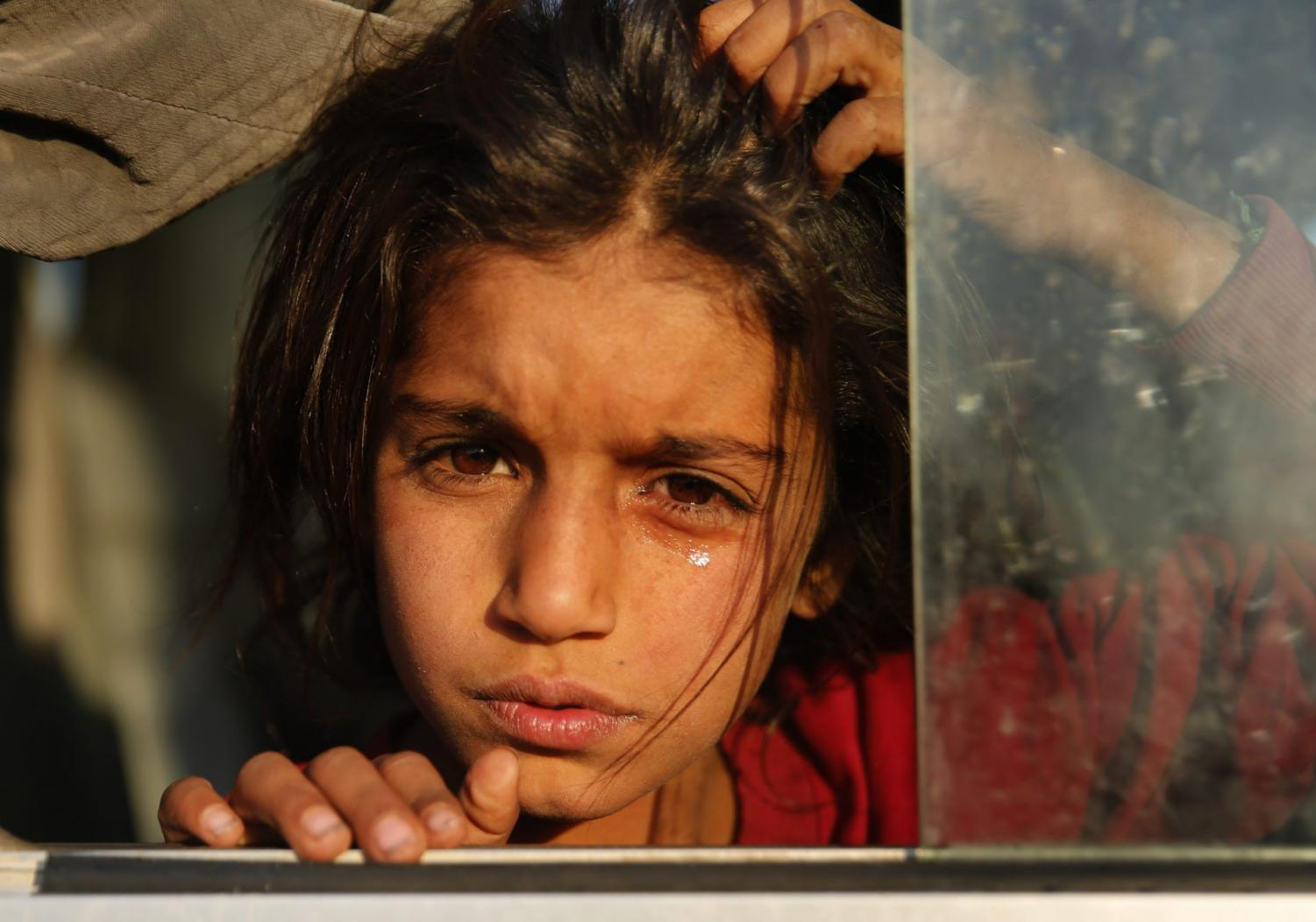 A Syrian girl who is newly displaced by the Turkish military operation in northeastern Syria, weeps as she sits in a bus upon her arrival at a camp in Mosul, Iraq, Wednesday, Oct. 16, 2019.