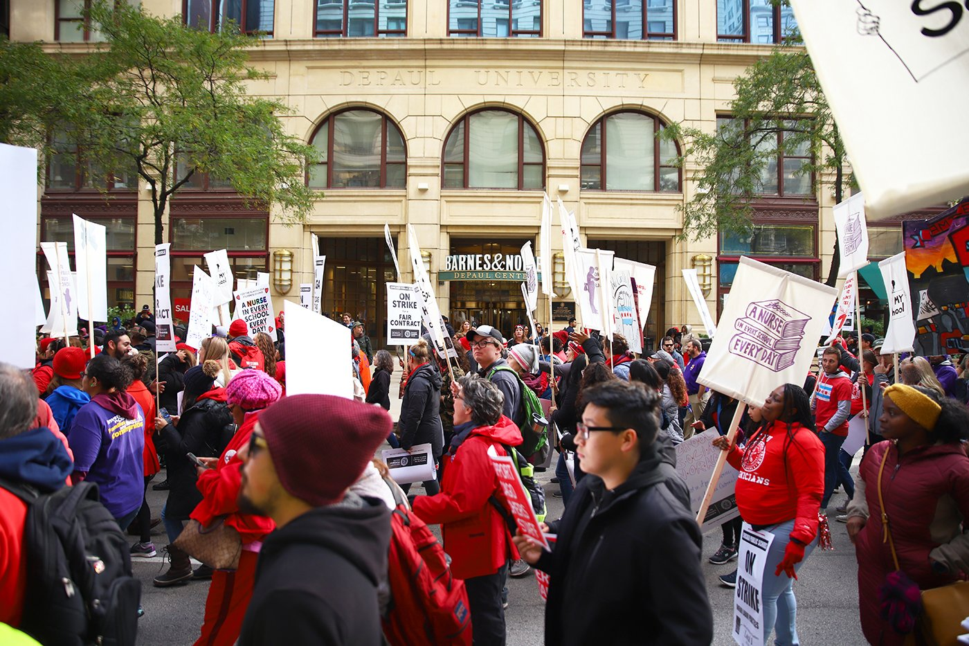 Members of the Chicago Teachers Union walk past the Loop's DePaul Center on Thursday, Oct. 17.