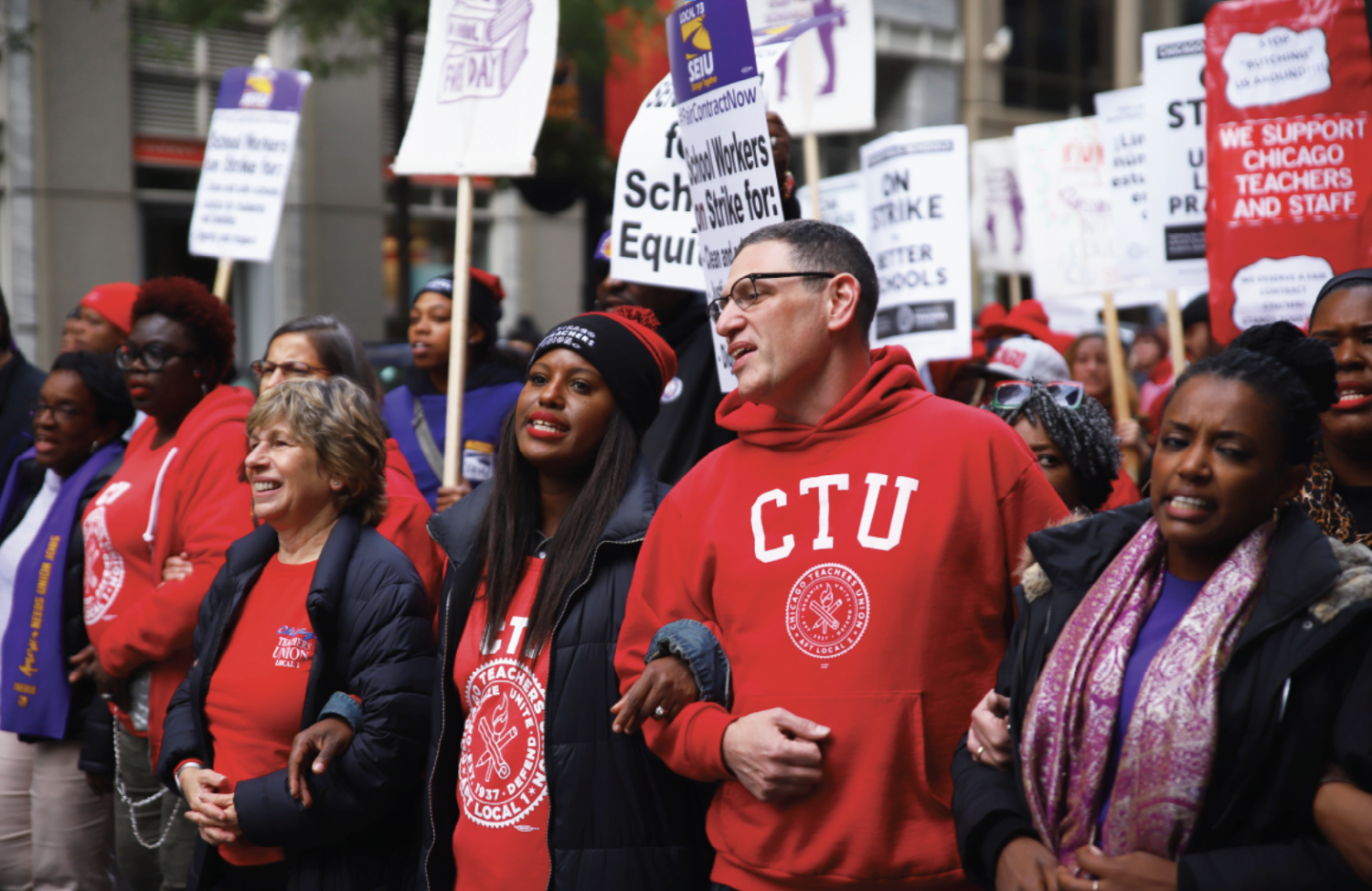 Chicago Teachers Union President Jesse Sharkey (center) and Vice President Stacy Davis Gates (left) join members of to walk the streets of Chicago on Thursday, Oct. 17.