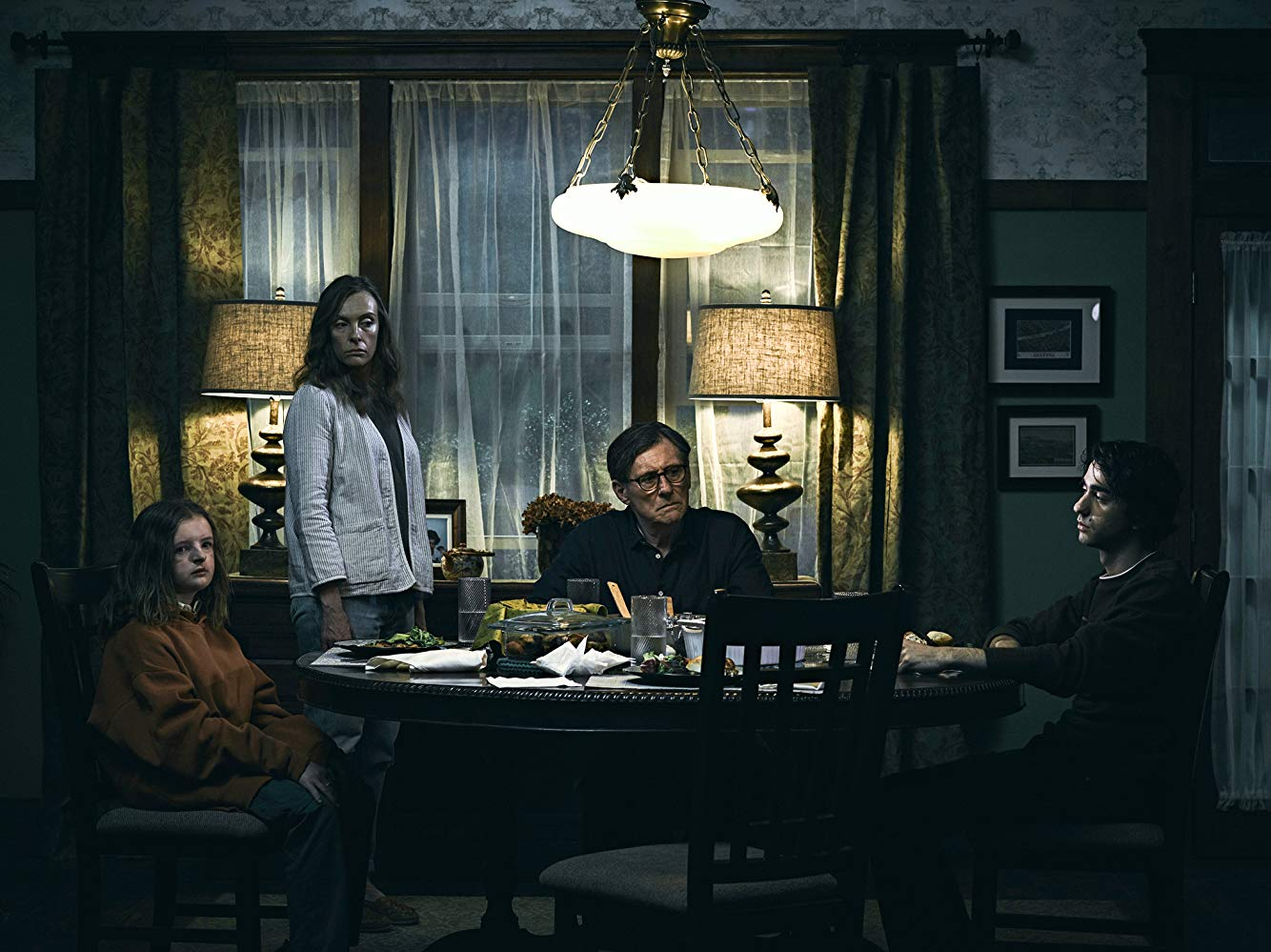 "The Graham family — Charlie (Milly Shapiro), Annie (Toni Collette), Steve (Gabriel Byrne) and Peter (Alex Wolff) — sit around the table in ""Hereditary."""