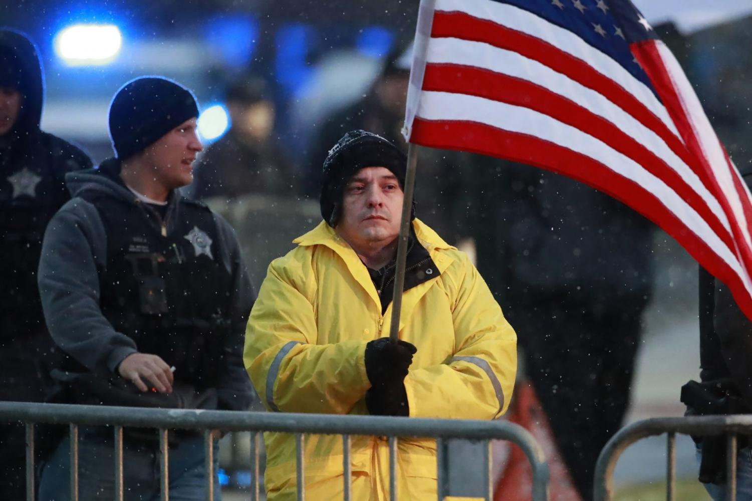 In this Nov. 25, 2018 file photo, State Rep. Jaime Andrade holds a flag outside the visitation for Chicago police Officer Samuel Jimenez at a funeral home in Des Plaines, Ill.A federal bribery charge against an Illinois legislator has led to questions about whether lawmakers be allowed to lobby other units of government. Illinois like most states allows legislators to lobby outside state government. Andrade said he registered as a Chicago lobbyist and started charging for his services when the state budget crisis from 2015 to 2017 forced lawmakers to go without paychecks.