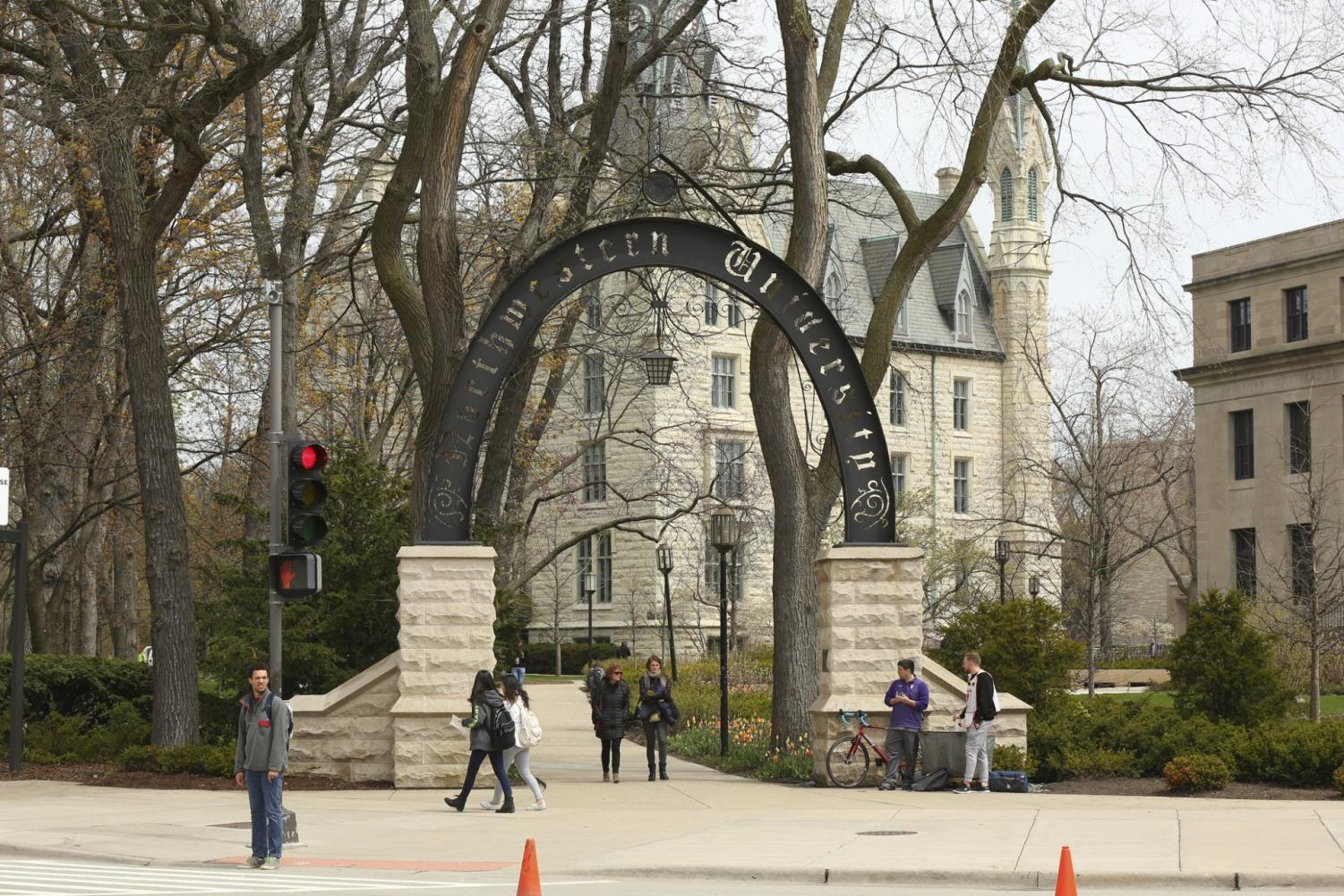 In this Friday, April 29, 2016, photo, people stand near the entrance gate to Northwestern University in Evanston, Ill. Northwestern University's student newspaper is under fire. Their first critics came from within the campus as student activists questioned journalists' coverage of protests. Within days, editors decided to write a statement apologizing but their editorial prompted a second round of criticism from journalists around the country starting Monday, Nov. 11, 2019.