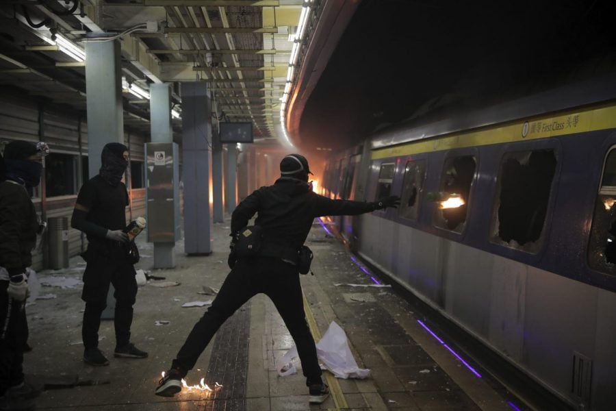A+student+hurls+a+molotov+cocktail+into+a+train+parked+inside+the+Chinese+University+MTR+station+in+Hong+Kong%2C+Wednesday%2C+Nov.+13%2C+2019.+Protesters+in+Hong+Kong+battled+police+on+multiple+fronts+on+Tuesday%2C+from+major+disruptions+during+the+morning+rush+hour+to+a+late-night+standoff+at+a+prominent+university%2C+as+the+5-month-old+anti-government+movement+takes+an+increasingly+violent+turn.