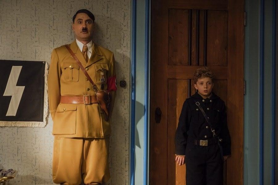 Taika Waititi (Hitler) hides with Roman Griffin Davis (Jojo Betzler).